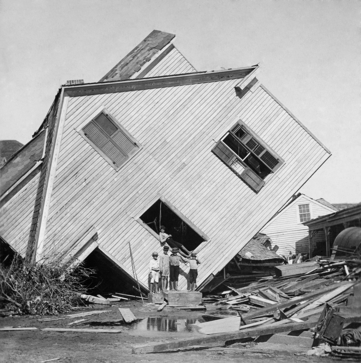 A house tipped on side after the 15 foot storm surge of the Galveston Hurricane of Sept. 1900. Five boys pose in front of the house on Avenue N
