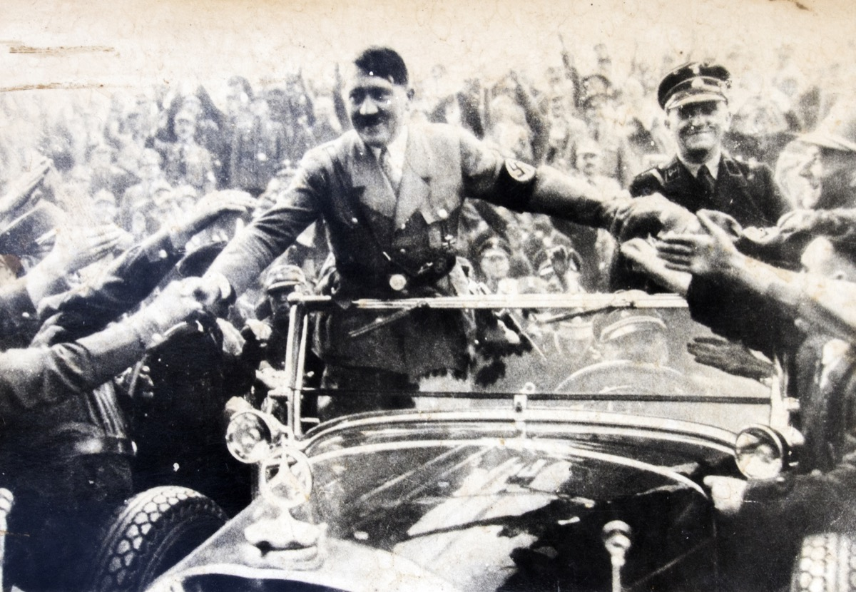 Adolf Hitler stands in a convertible and shakes hands with his followers
