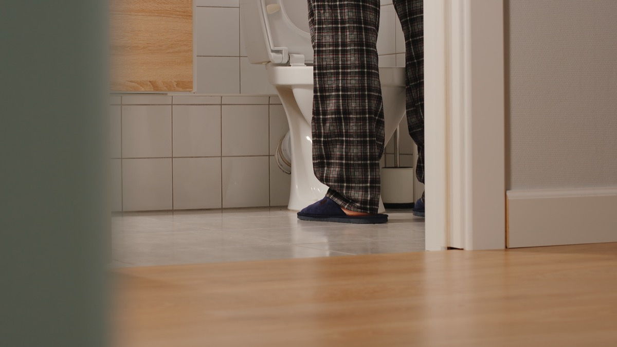 man's legs in pajamas while he pees in a toilet