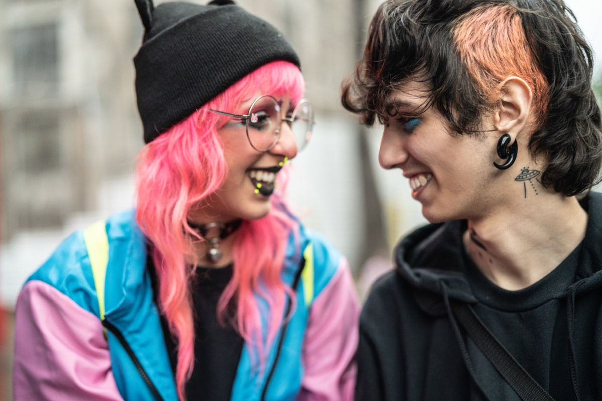 young white woman with pink hair smiling at young white man with piercings