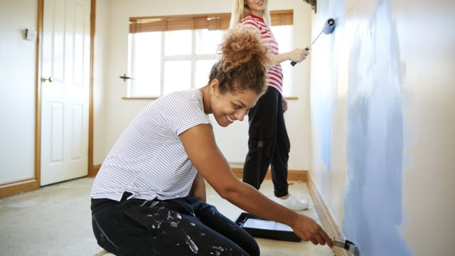 young black woman and young white woman painting a wall of their home blue