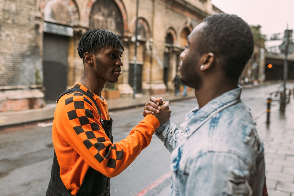 young black man shaking hands on the street