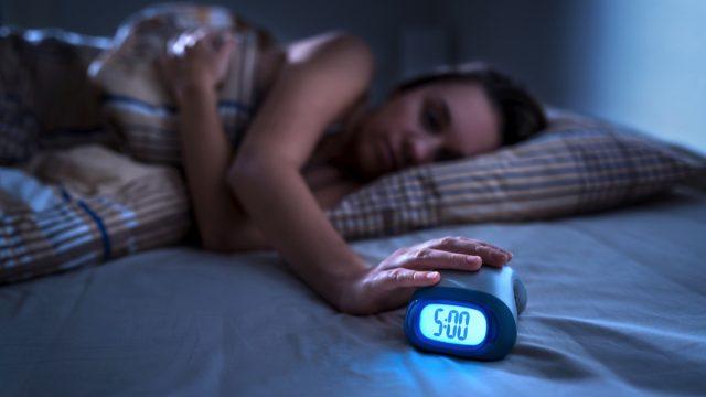 woman hitting alarm clock at 5 a.m. in the dark