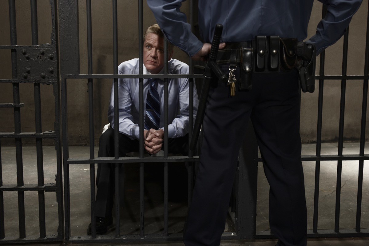 middle aged white man with tie sitting in jail cell with guard standing by
