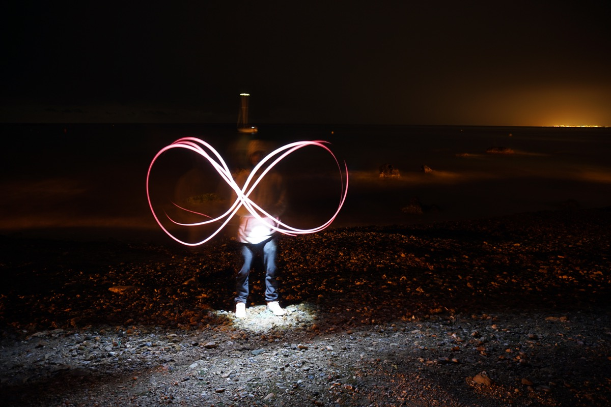 Man making an infinity sign with sparks from a sparkler