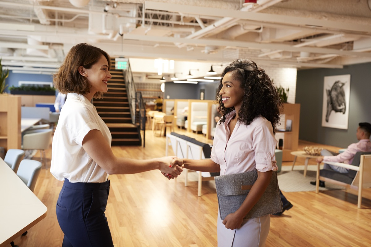 woman interviewing for a new job and shaking hands with another woman