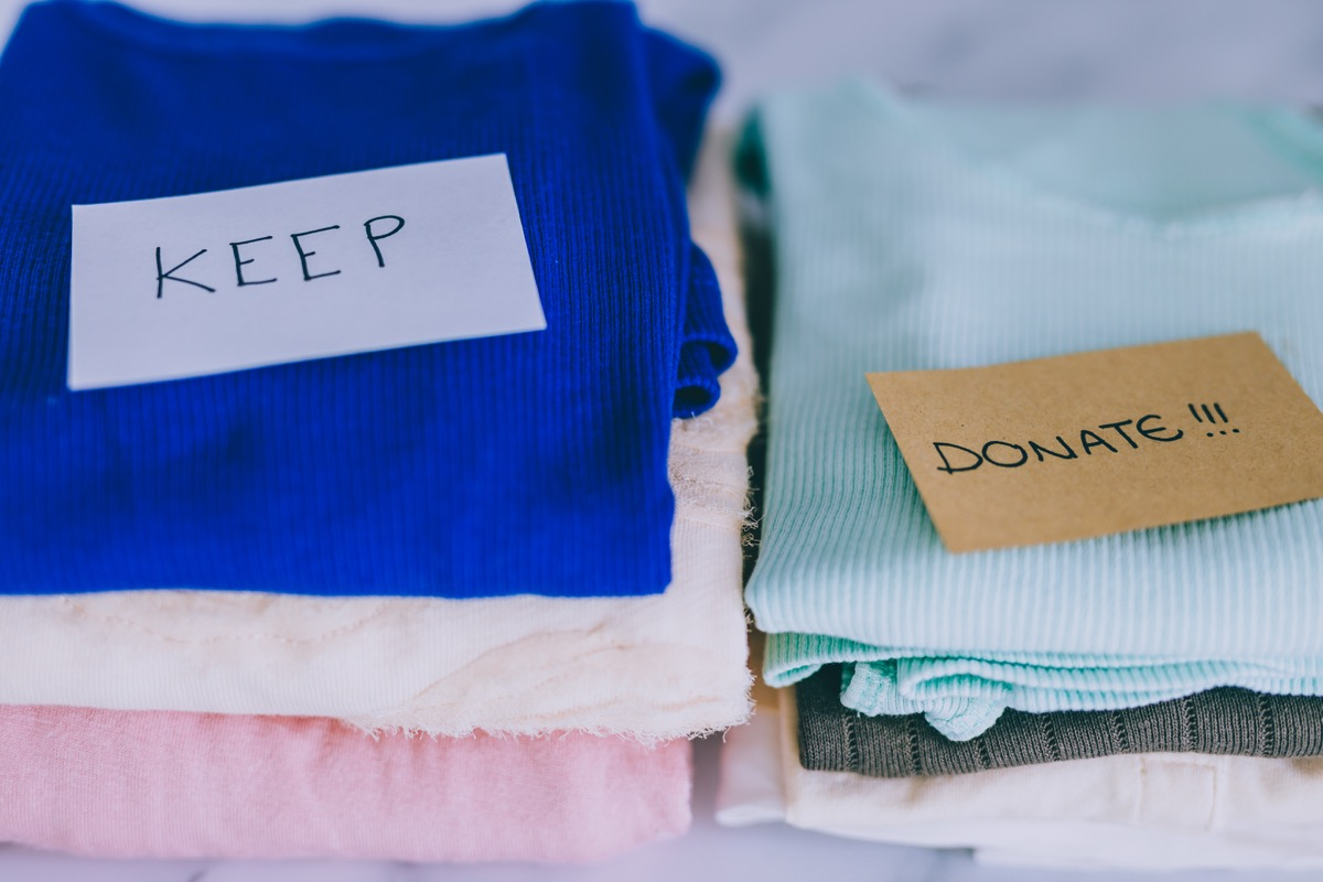 Keep and donate piles of clothes decluttering closet