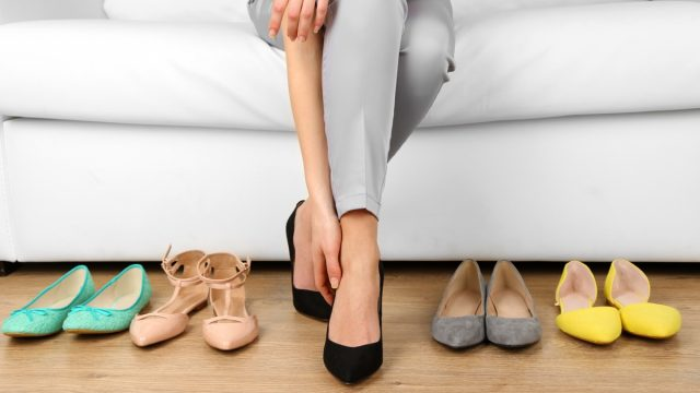 Trying on shoes by elegant lady sitting on white sofa background {Save Money on Shoes}