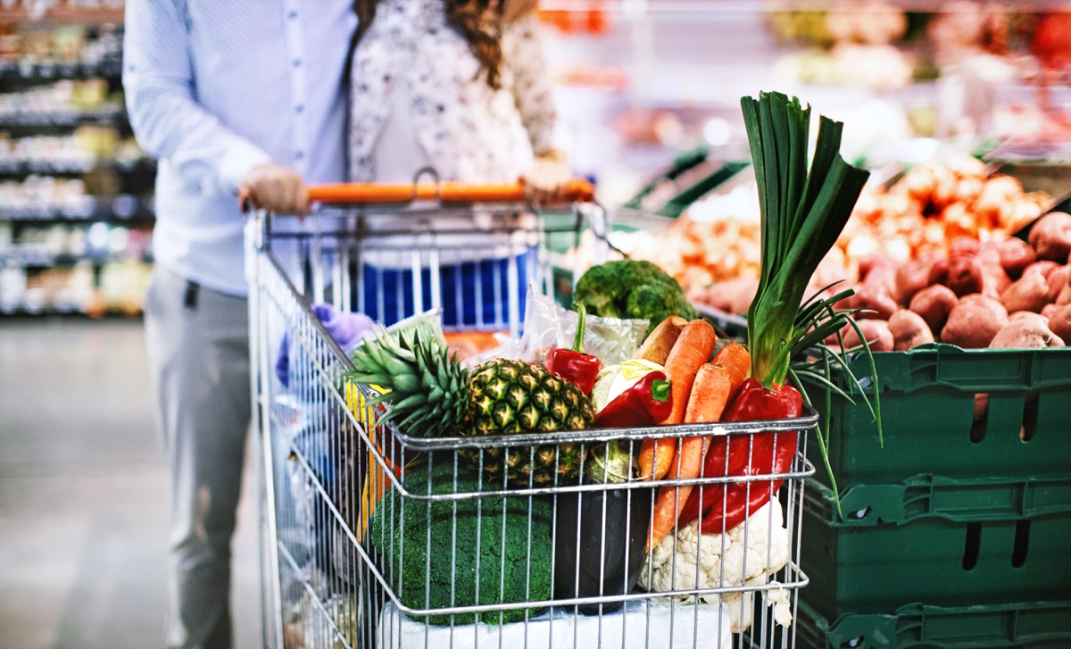 couple with filled grocery shopping cart