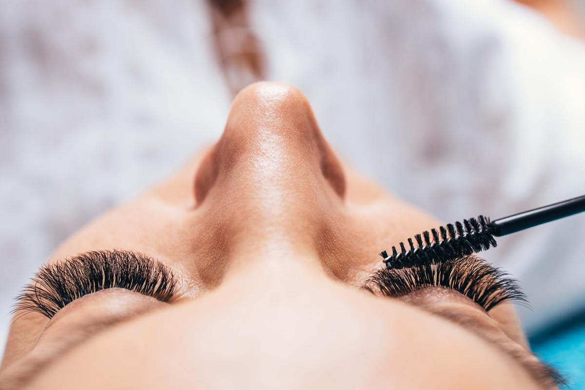 Woman applying mascara to lash extensions makeup