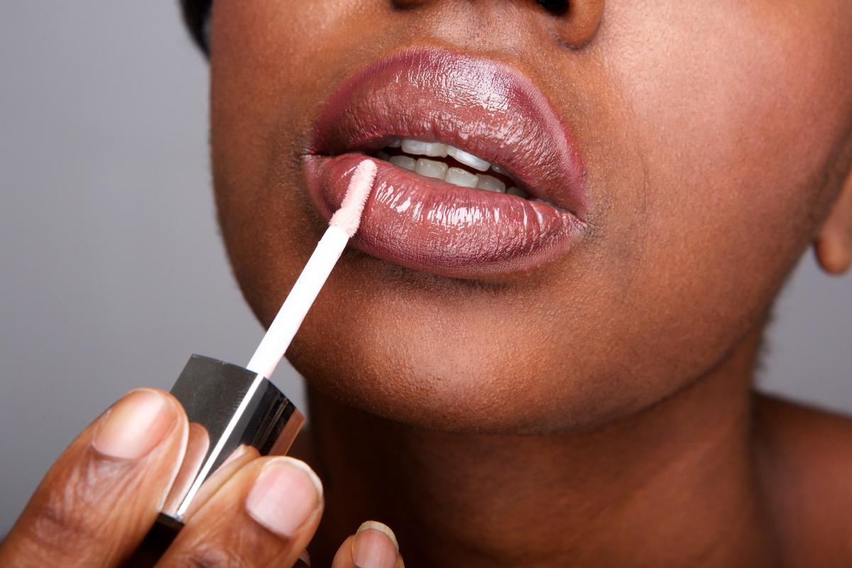 Woman applying lip gloss clouse up