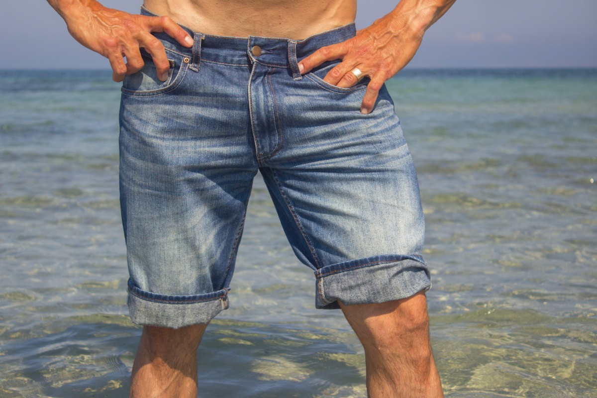 Man wearing jeans shorts standing in the sea water, legs closeup