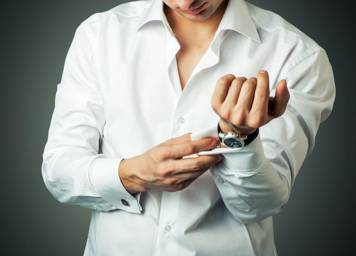 man buttoning a white french cuff shirt