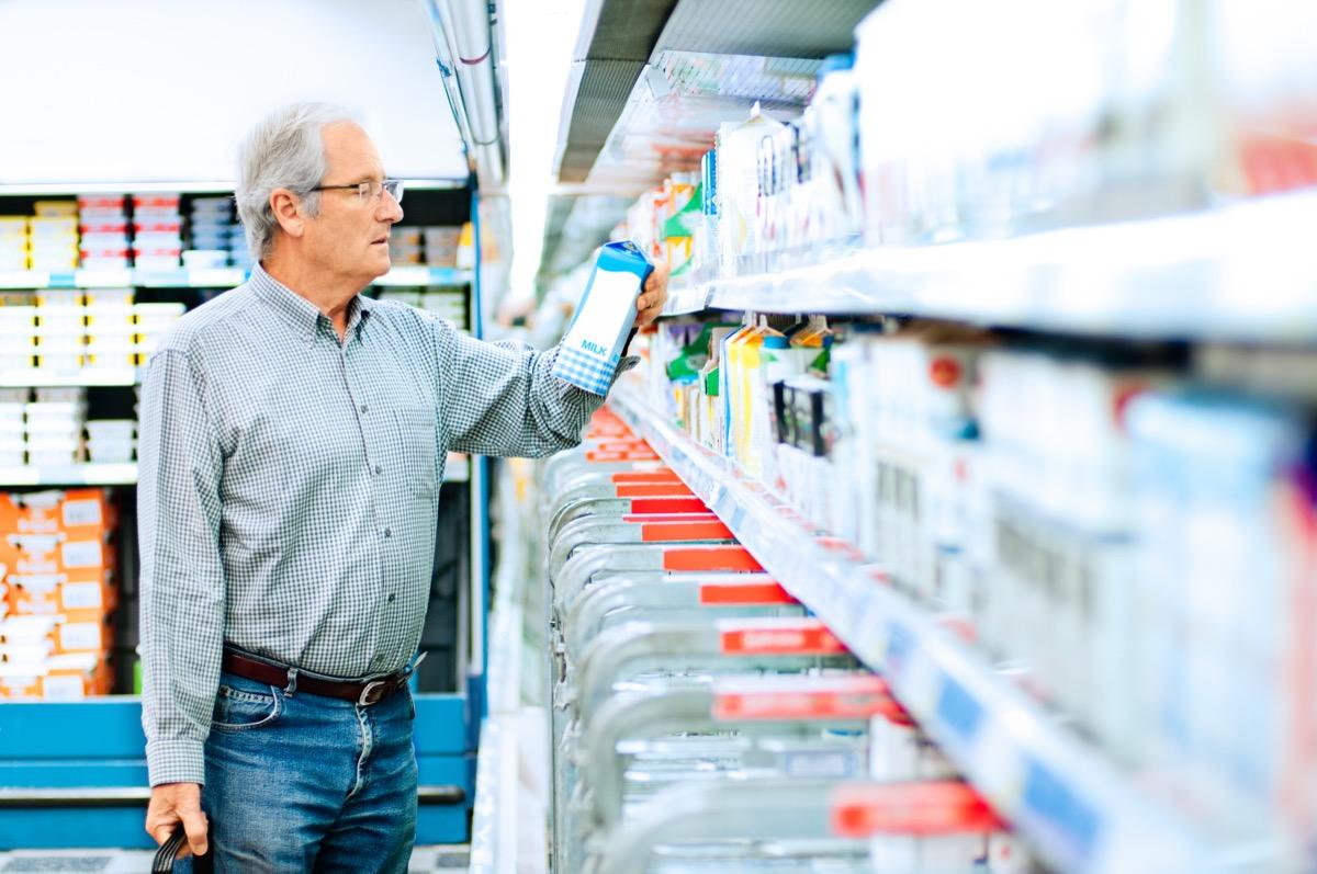 man buying milk in supermarket