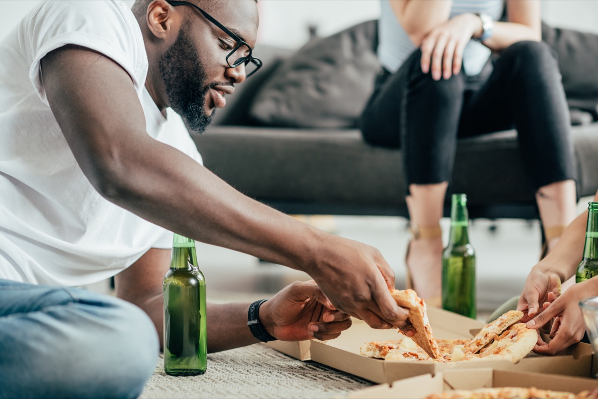 man eating pizza and drinking beer on floor, healthy sex after 40