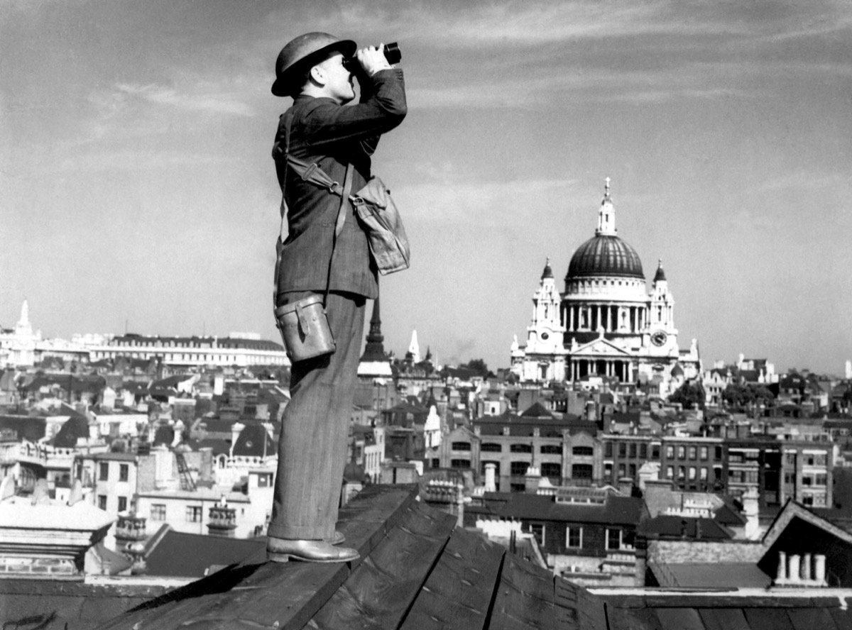 Aircraft spotter searches the sky with binoculars during the Battle of Britain. St. Paul's Cathedral is in the background. World War 2