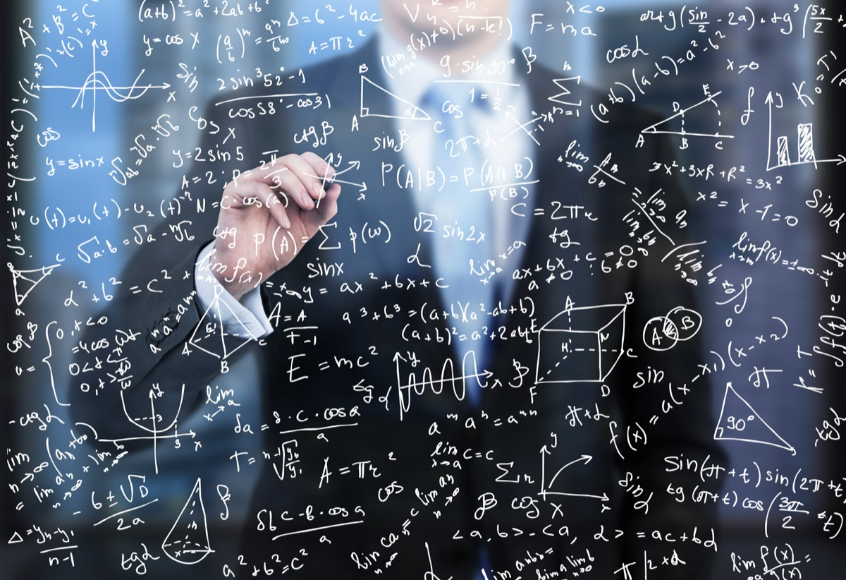 Man doing math equations on a board