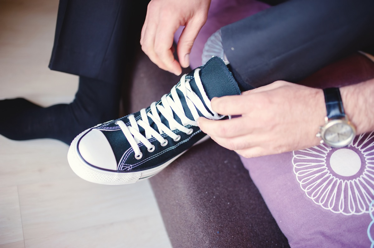 man putting on converse shoes while wearing a suit