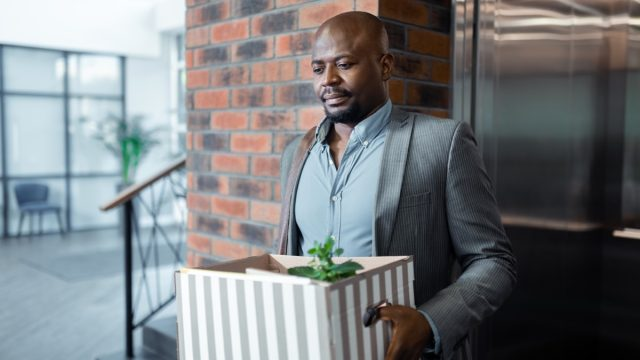 man leaving work with box after quitting job