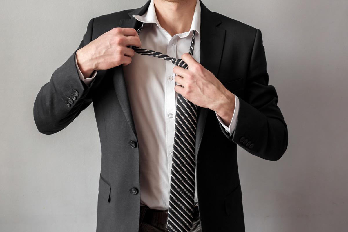 man retying a striped tie