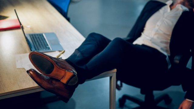 man kicking his feet up on a desk and sleeping in the office