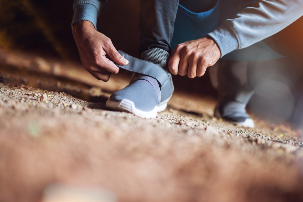 Man adjusting velcro exercise sneakers before his run