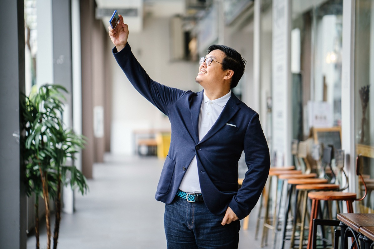 man wearing a blue blazer and dark jeans holding a smartphone and talking a selfie