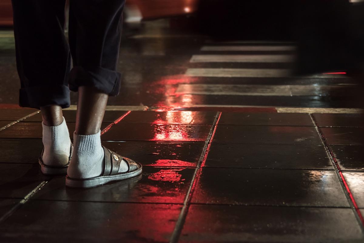 man wearing socks and sandals at night