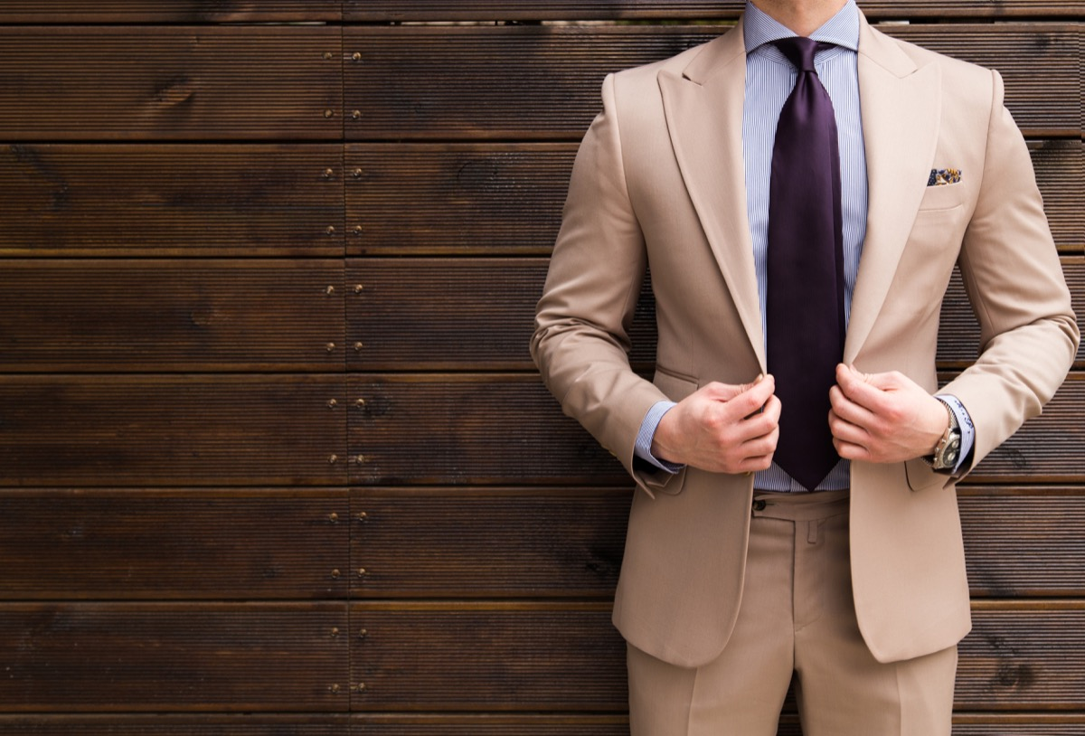 man wearing a tan suit and a purple tie