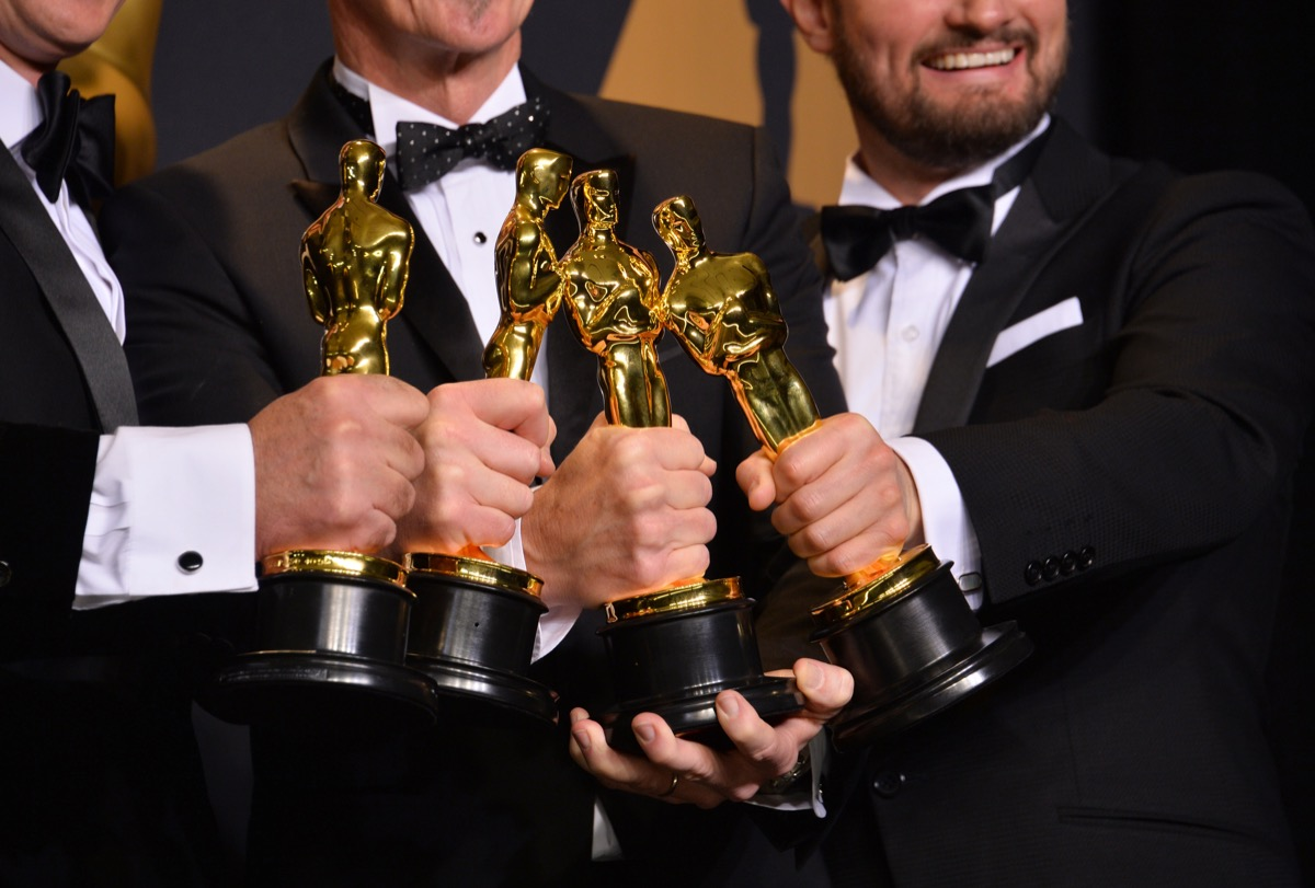 men holding oscars statues