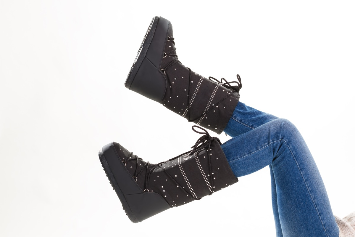 Fun black winter moon boots. Legs of girl in jeans and moon boots on white background. - Image