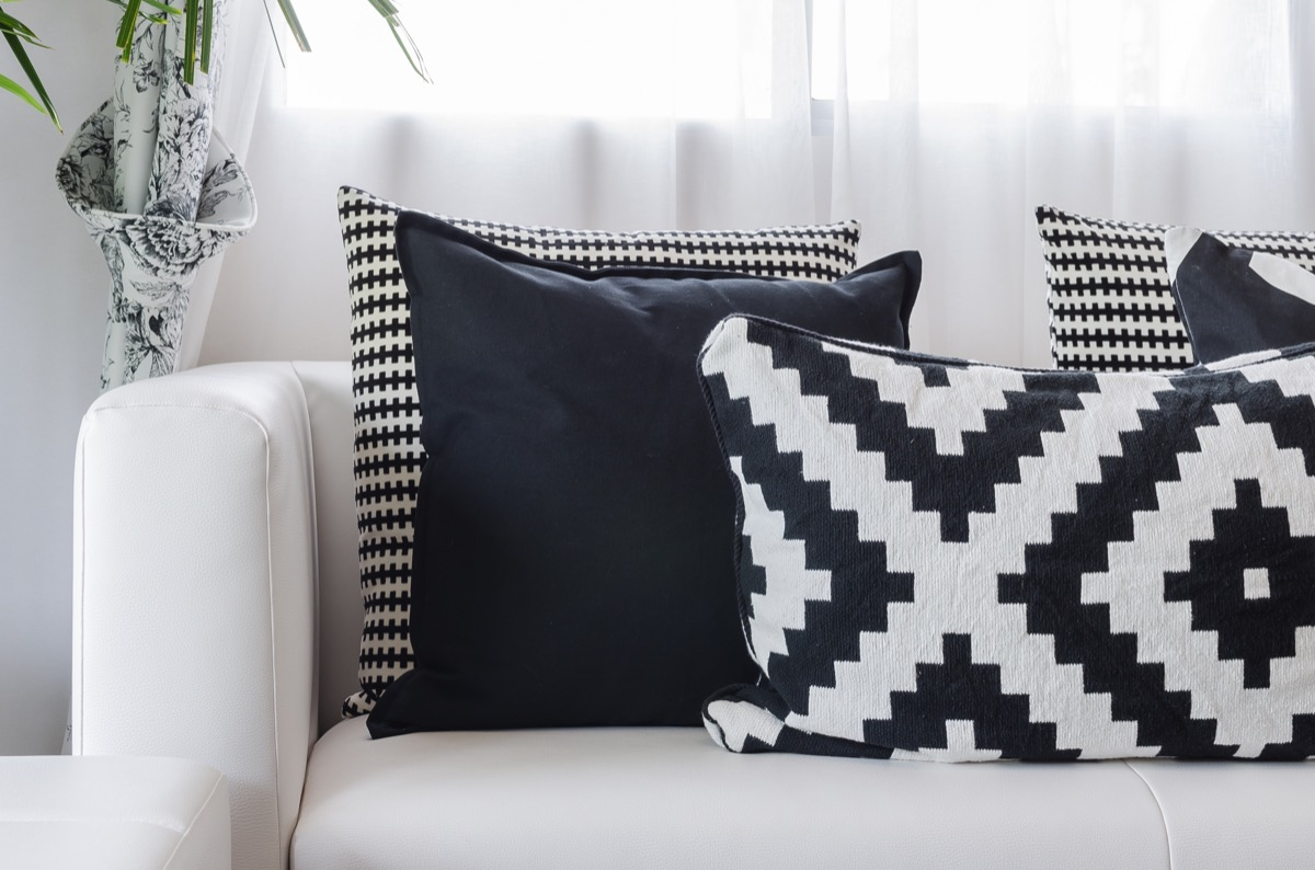 Multiple different black and white patterned pillows resting on a white couch