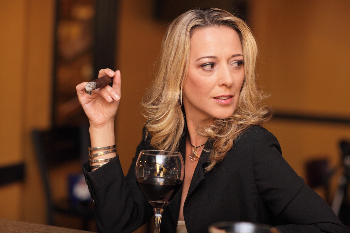 Attractive woman with a cigar and a drink