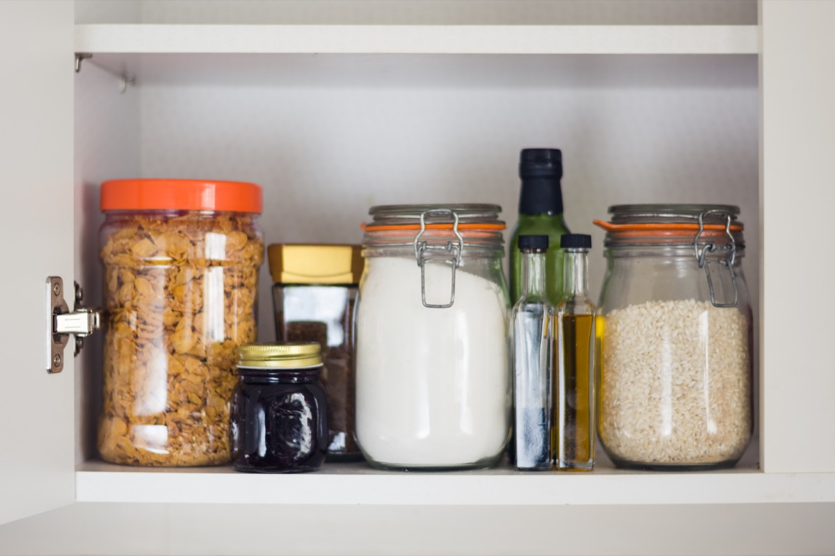 Organized pantry jars in cabinet