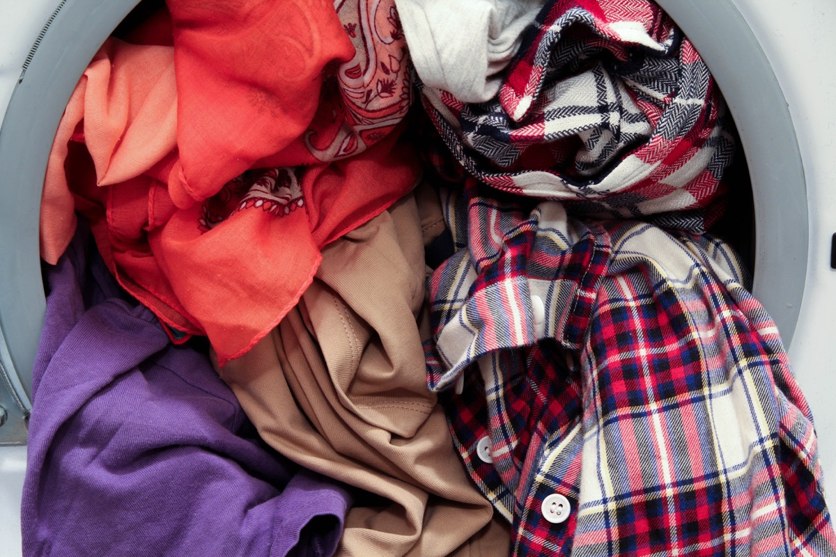 Front loading washing machine overloaded with colorful dirty clothes, close up view - Image