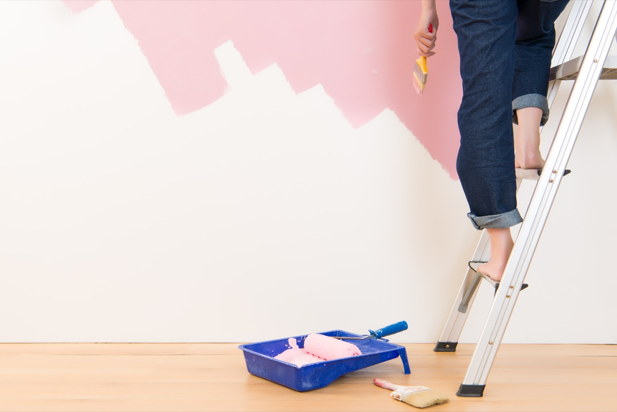 young woman standing on ladder doing wall painting.