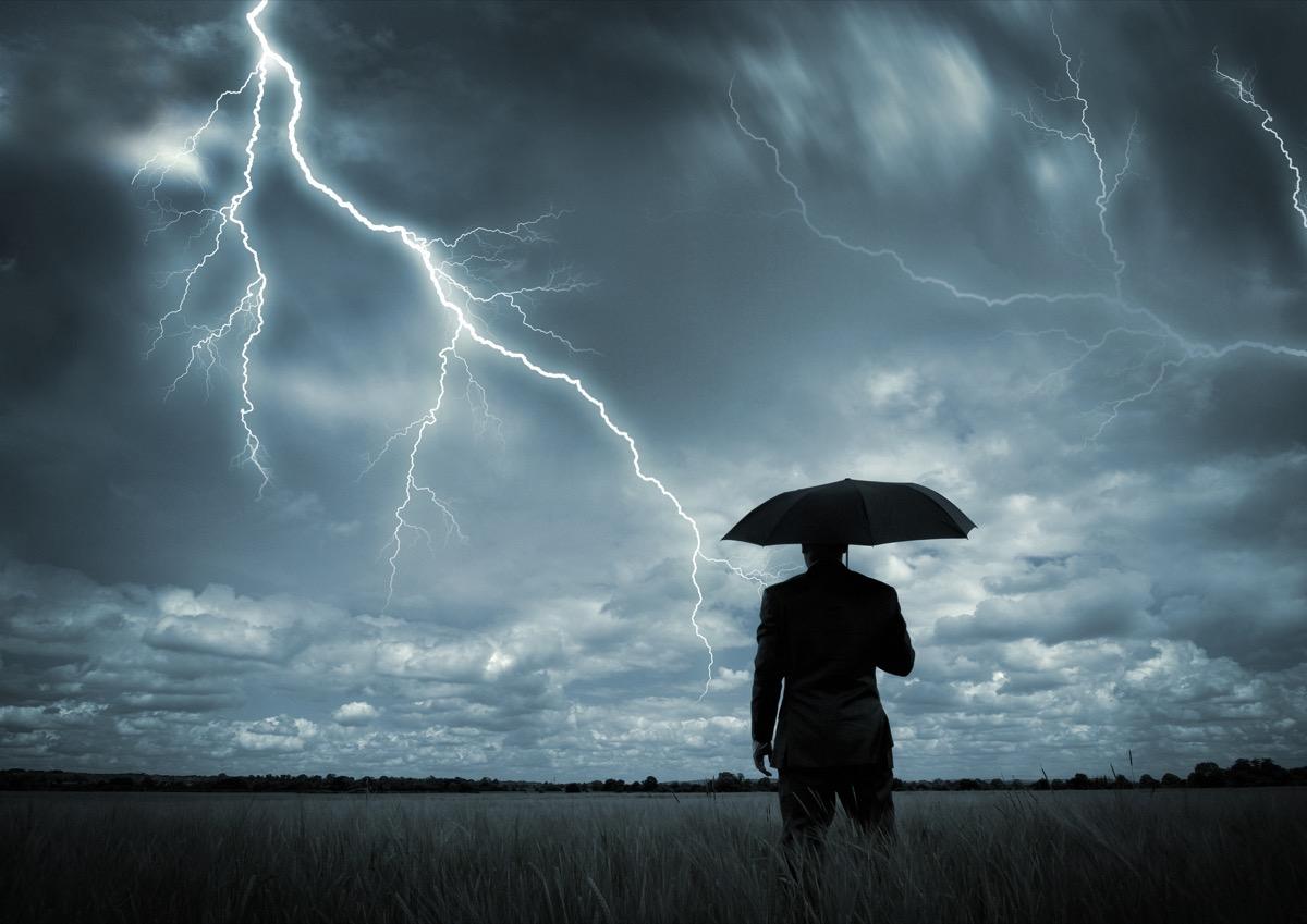 A businessman holding an umbrella in a storm