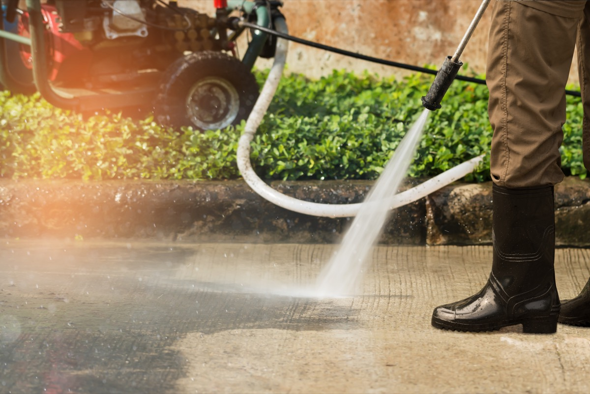 Worker cleaning driveway with gasoline high pressure washer splashing the dirt,professional cleaning services.High pressure cleaning, lower body.