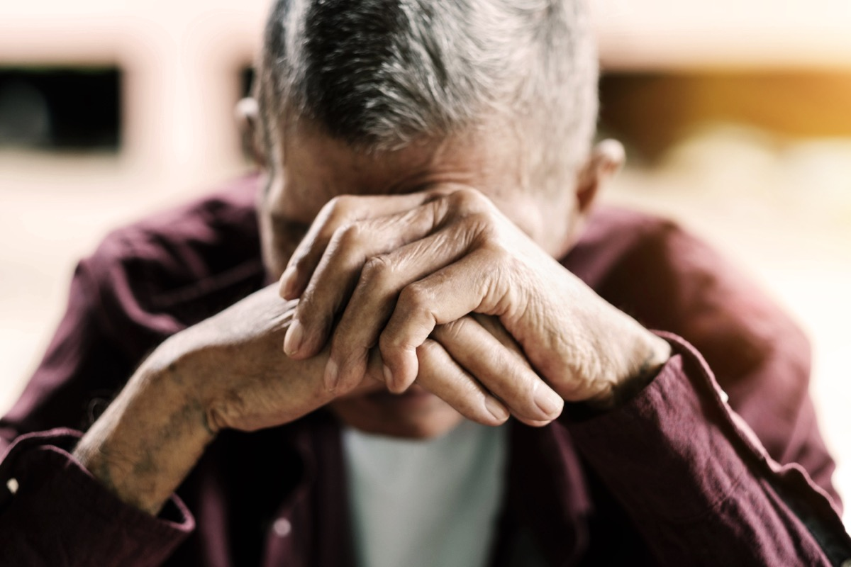 Sad older man with his head in his hand