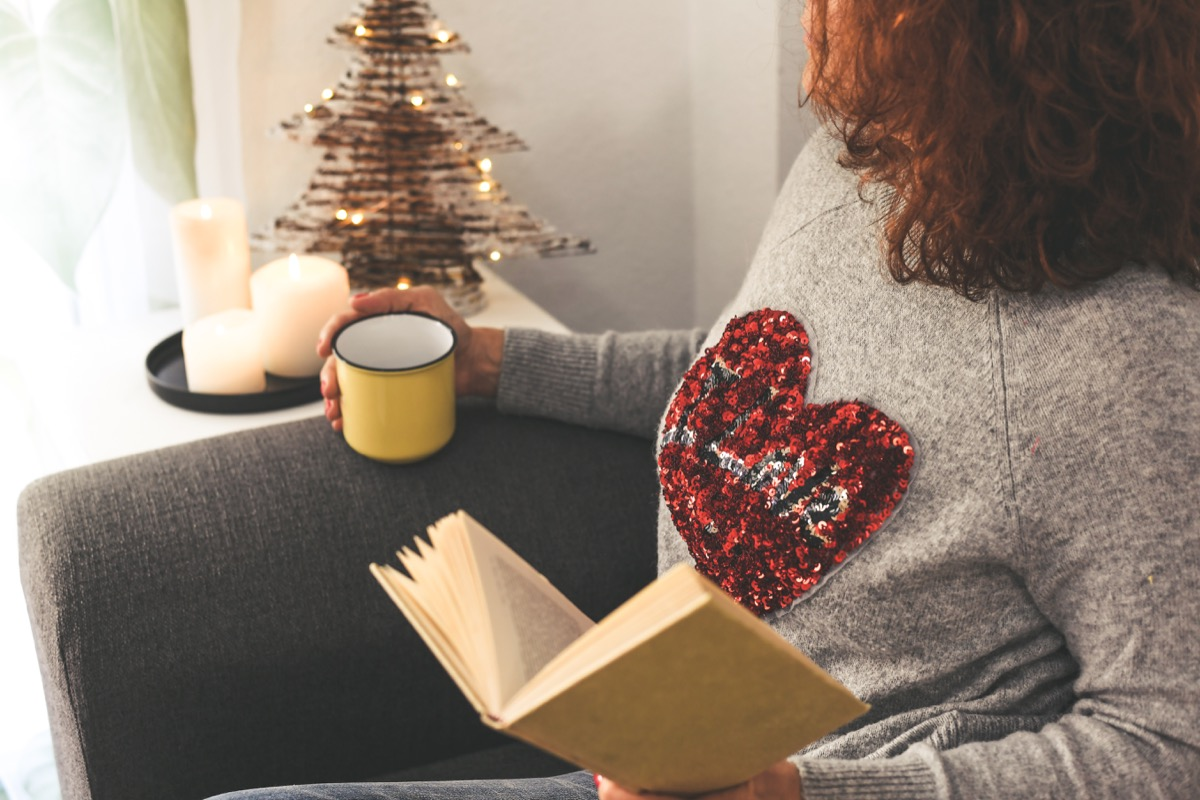 Woman wearing sequin heart t-shirt while drinking tea and reading a book