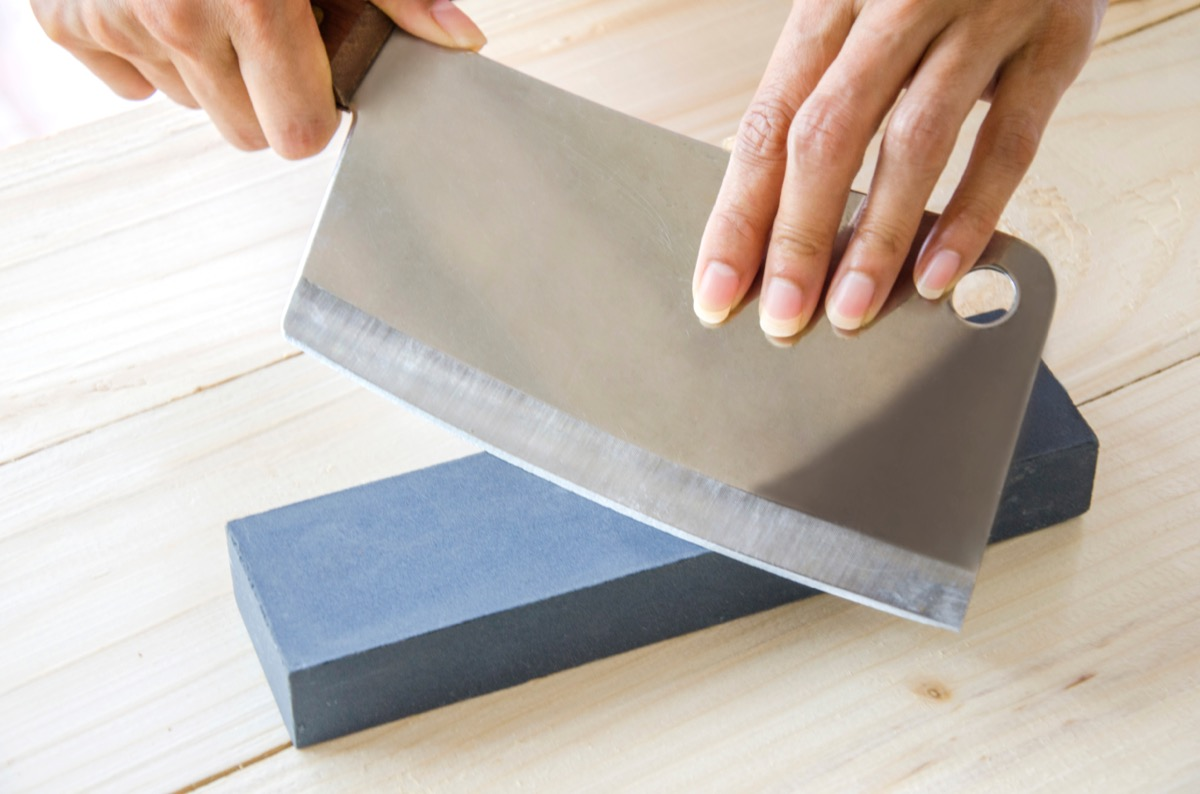 Person sharpening a knife cleaver