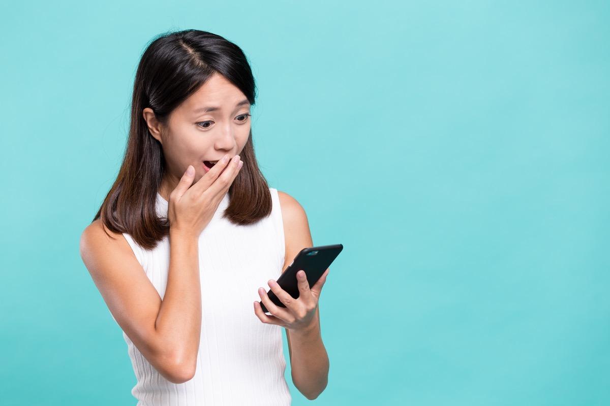 Shocked woman looking at phone