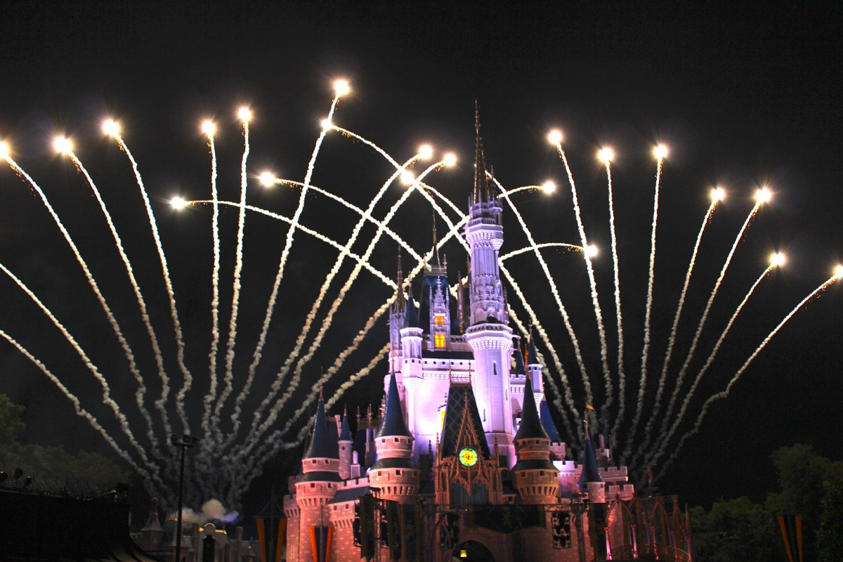 Cinderella Castle lit up at night in Magic Kingdom with fireworks behind it, Disney Facts