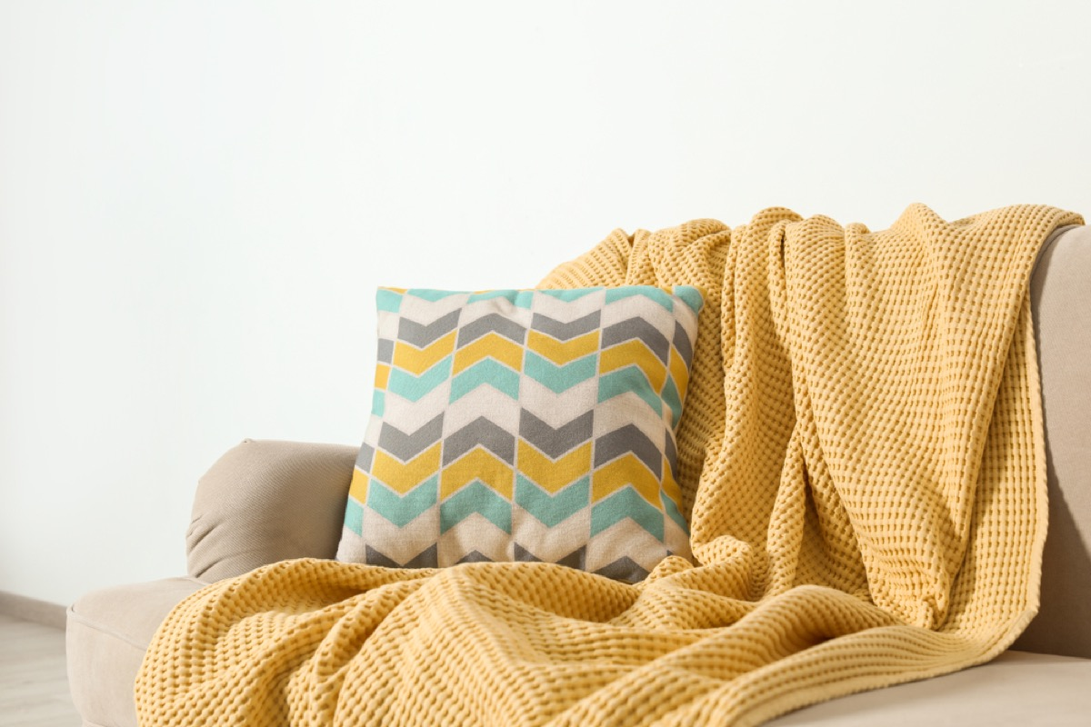 yellow throw blanket and patterned pillow on a couch