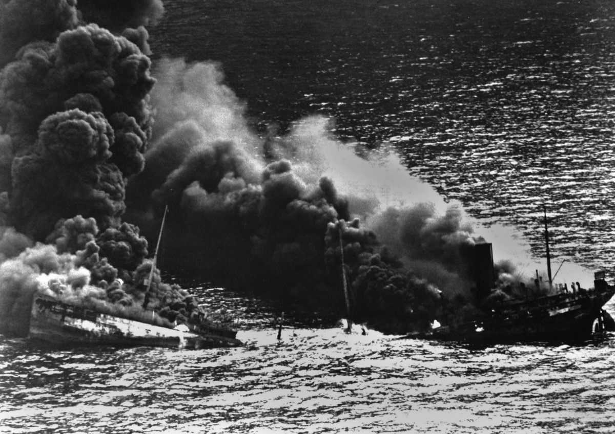 Allied tanker torpedoed in Atlantic Ocean by German submarine during World War 2. The ship crumbled amidships under heat of fire as she settled toward bottom of sea. 1942.