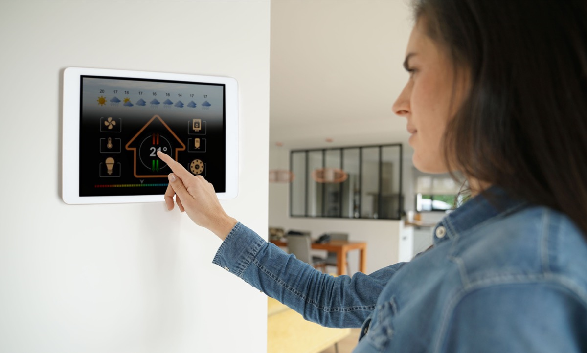 Woman using smart technology thermostat in her home