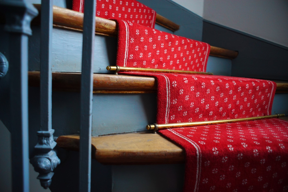 Golden stair rods on a red carpeted staircase