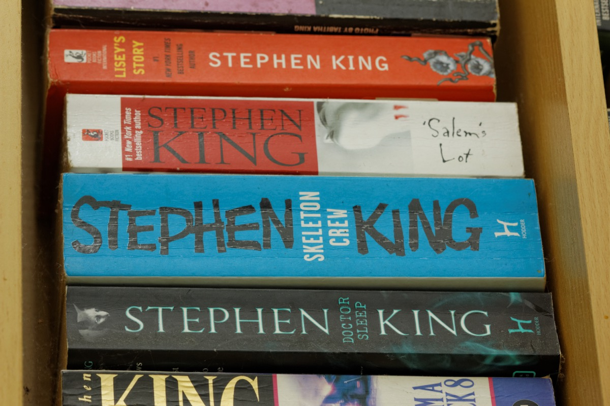 JOHOR,MALAYSIA - JULY 28, 2016: Assorted books written by famous thriller author Stephen King on display in wooden rack.