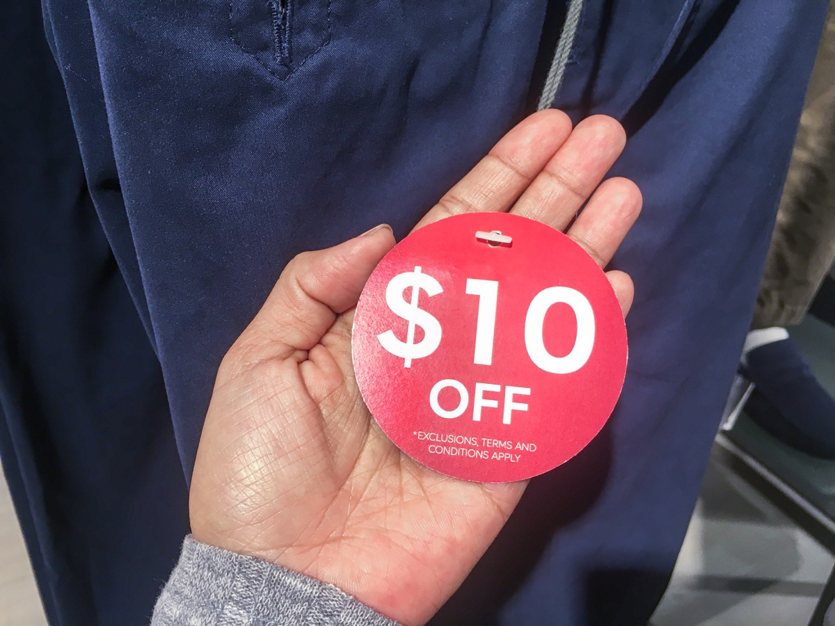 woman holding $10 off sale