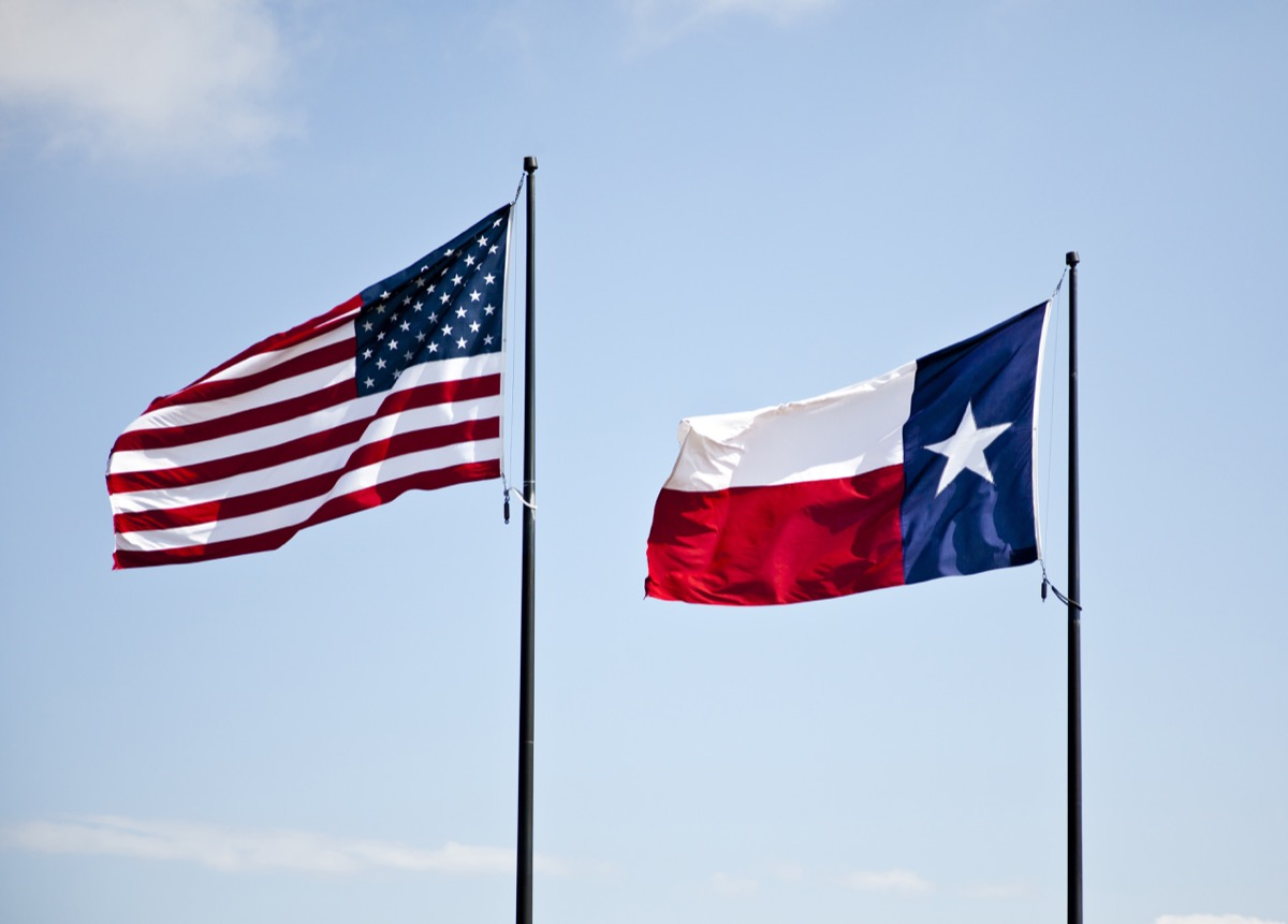 The American and Texas flags flying high together against a blue lightly cloudy sky